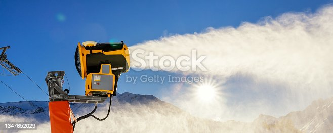 istock Operating artificial snow cannon near piste making snowy powder.Ski lift ropeway on hilghland alpine mountain winter resort on bright sunny day. downhill slopes with people enjoy sport activities 1347652029