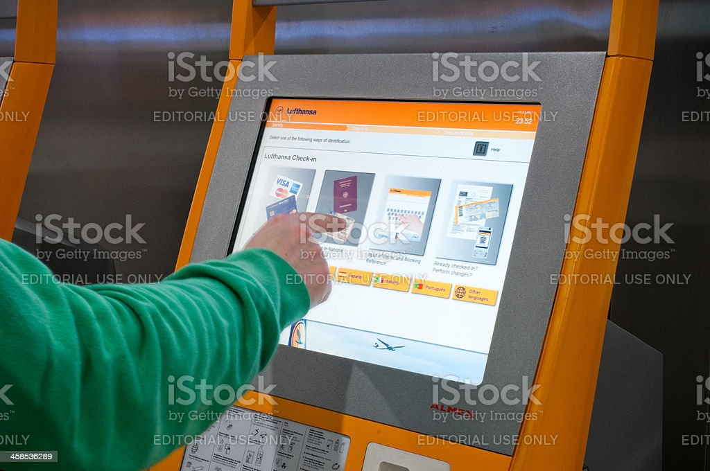 Operating Lufthansa electronic self check-in ticket machine stock photo