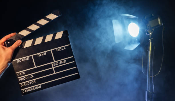 Operator holding clapperboard, studio light on background stock photo