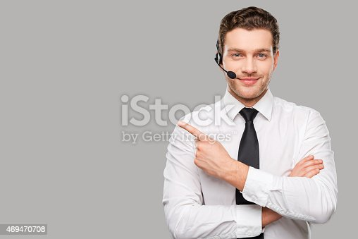 Handsome young man in formalwear and headset looking at camera and pointing away while standing against grey background