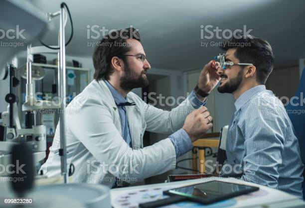 Ophthalmologist doing an eyesight exam of a young man with trial picture id699823280?b=1&k=6&m=699823280&s=612x612&h=psfjyjebjlaxu7517fv9x432nivgs0rrdelwu8uvppe=