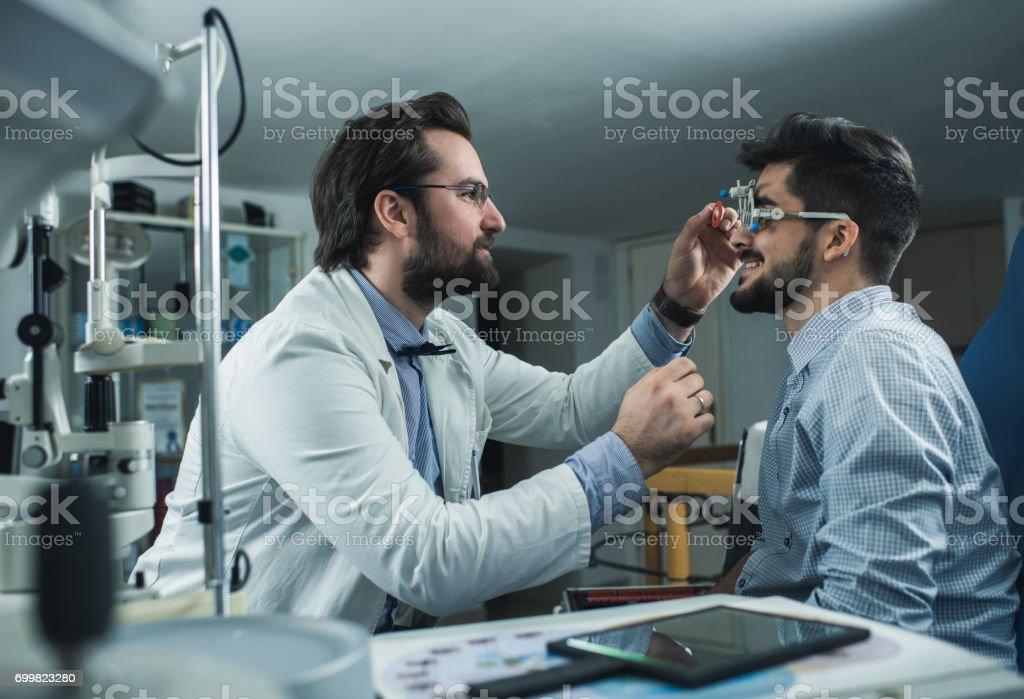 眼科医は、試験フレームを持つ若者の視力試験を行います。 ストックフォト
