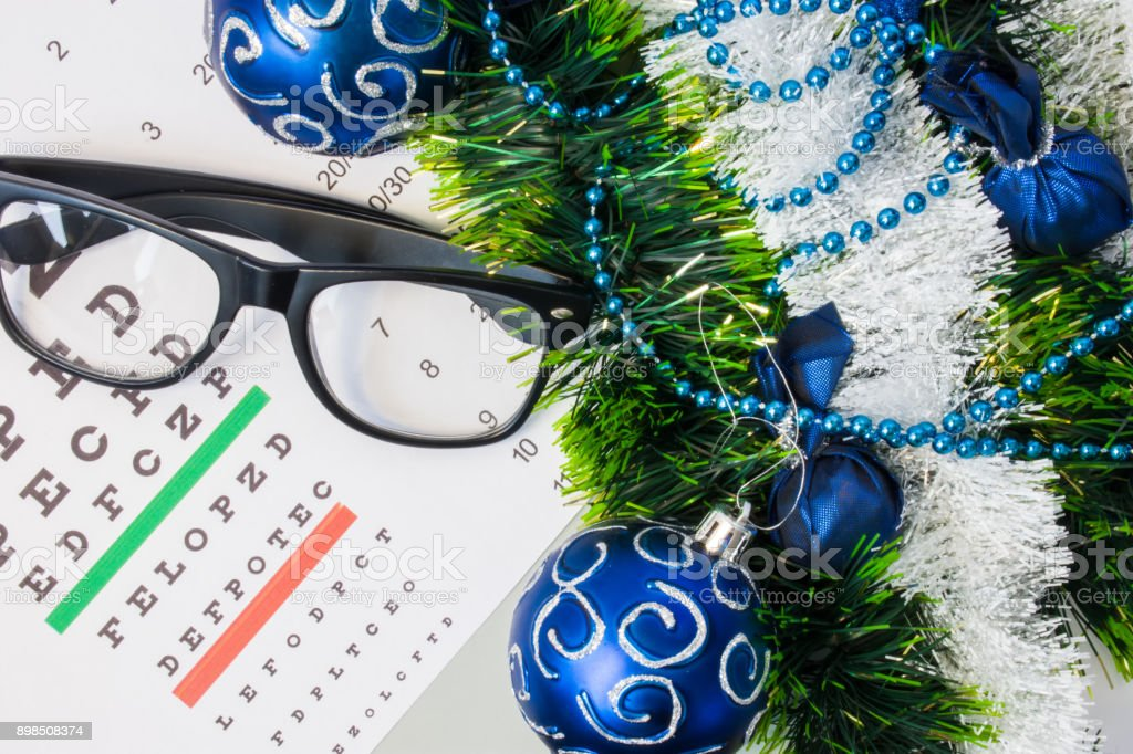 Ophthalmology or optometry Christmas and New Year with decorations. Eyeglasses and table for measure visual acuity lying near artificial snow with glitter, toys and blue balls on Christmas tree stock photo