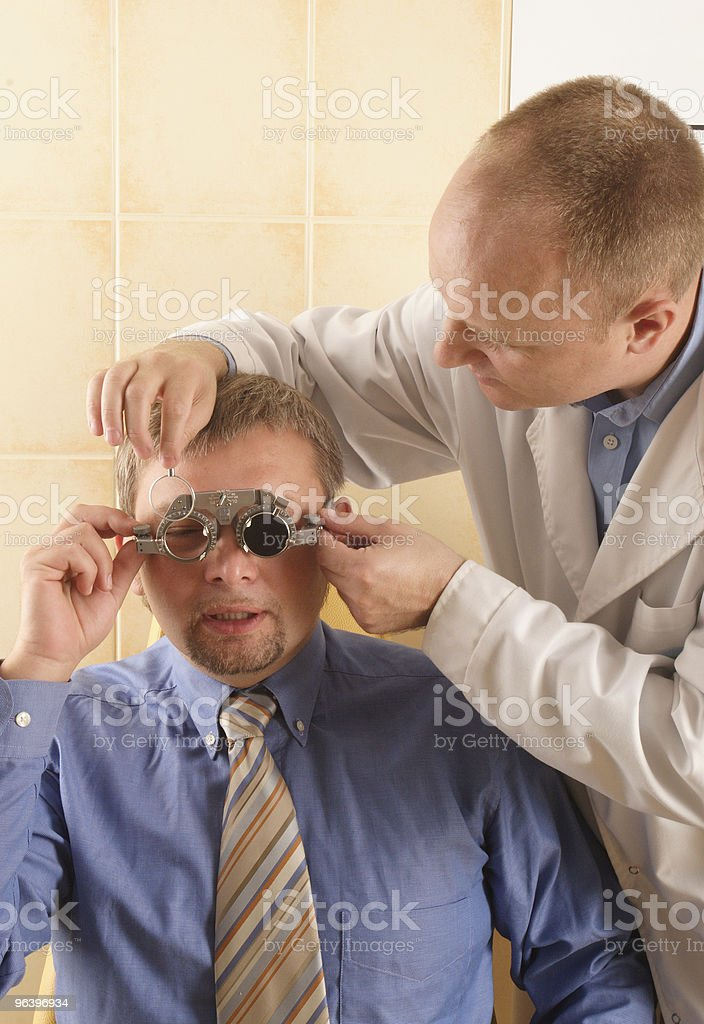 opician performing eye examination - Royalty-free Adult Stock Photo