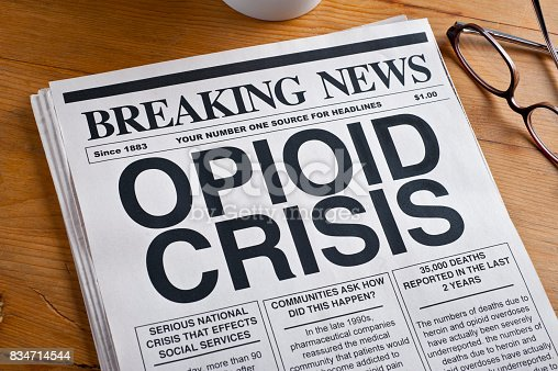istock Opioid Crisis Newspaper Headline. Newspaper is on a Desk 834714544