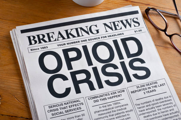 Opioid Crisis Newspaper Headline. Newspaper is on a Desk stock photo