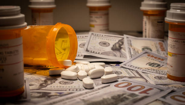 Opioids and US Currency Prescription medication is strewn out upon US currency. smuggling stock pictures, royalty-free photos & images