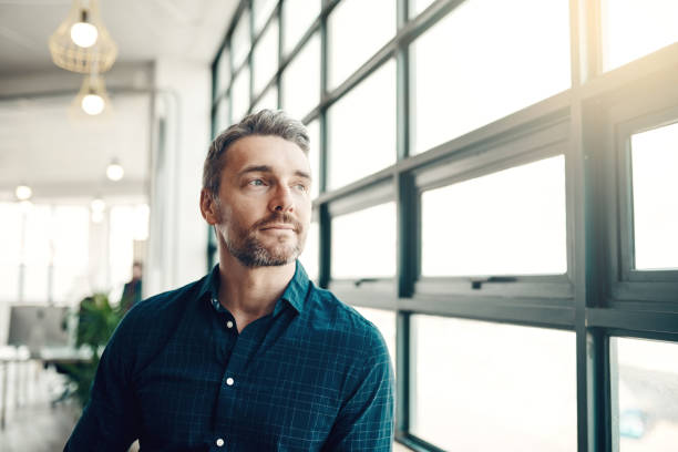 Opportunity doesn't hang around, neither should you Shot of a mature businessman looking thoughtfully out of an office window reflection stock pictures, royalty-free photos & images
