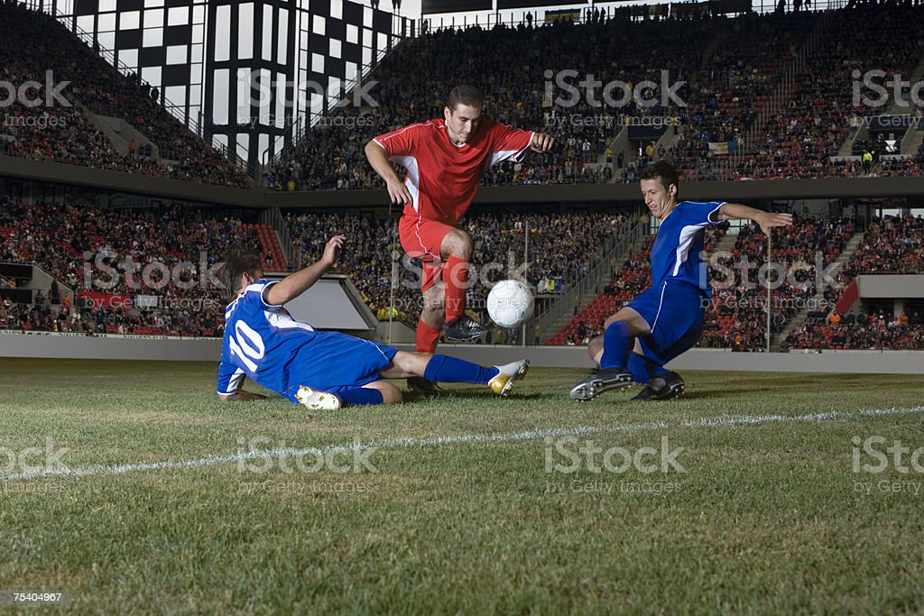 Opposite players tackling footballer stock photo