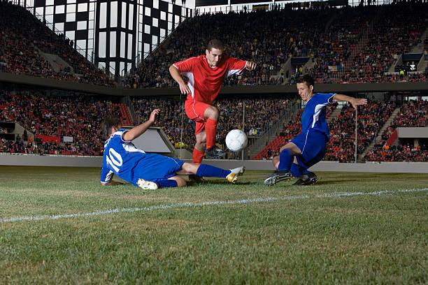 Abordar footballer frente a los jugadores - foto de stock