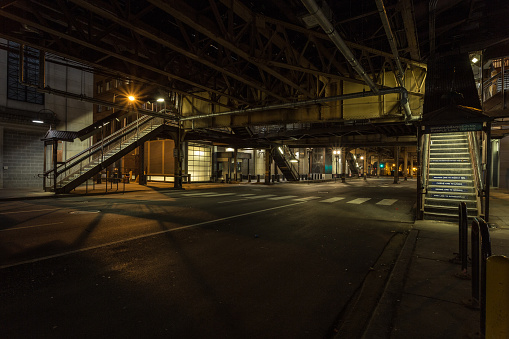 Opposite stairwells leading up to overhead subway trains at night in downtown Chicago