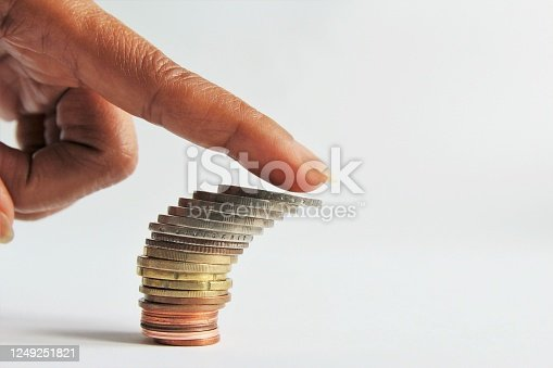 Close up index finger pushing on top of stack of money coins are about to fall down. photo isolate on white side view copy space