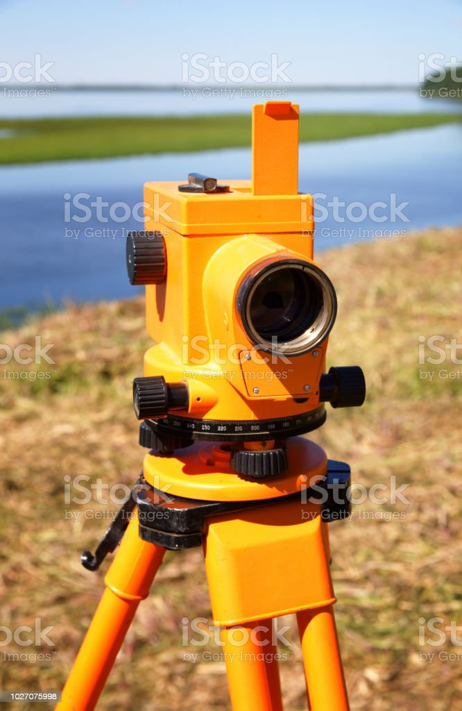 The optical level is mounted on a tripod close-up. In the background,...