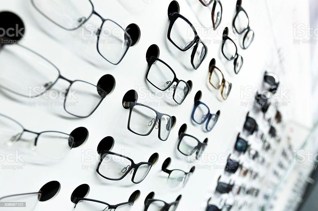 optical store, wall of many fashionable eyeglasses stock photo