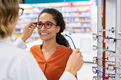 African young woman in optic store choosing new cool-down glasses with optician. Mixed race girl trying new eyeglasses with the help of the pharmacist. Happy multiethnic woman trying new rest spectacle frame in optic store: eyesight and eye care concept.