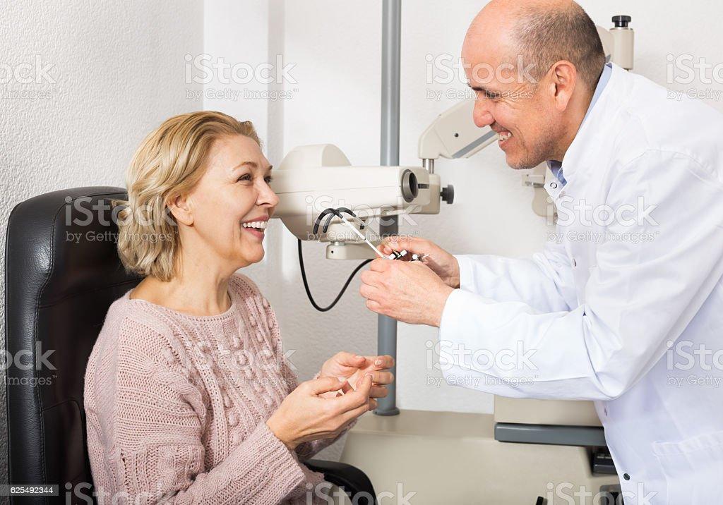 Optician doing eye check up to woman stock photo
