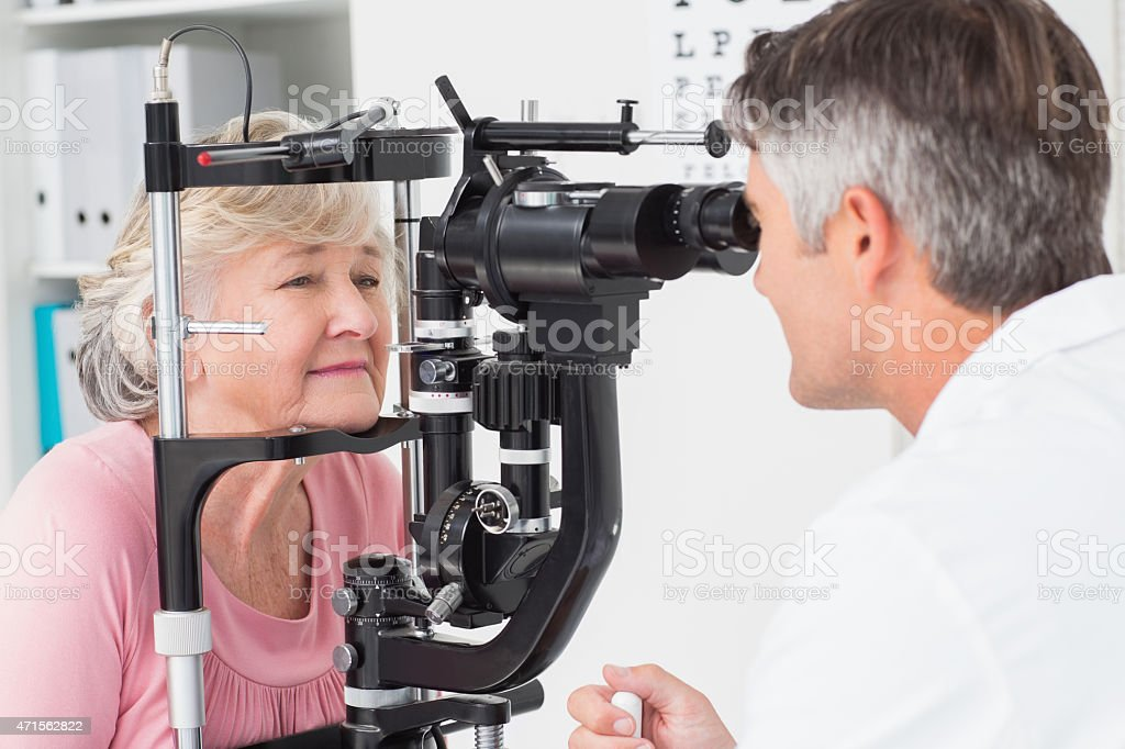 Optician examining senior female patient through slit lamp stock photo