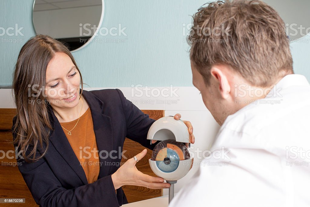 Optician explaining eye structure stock photo
