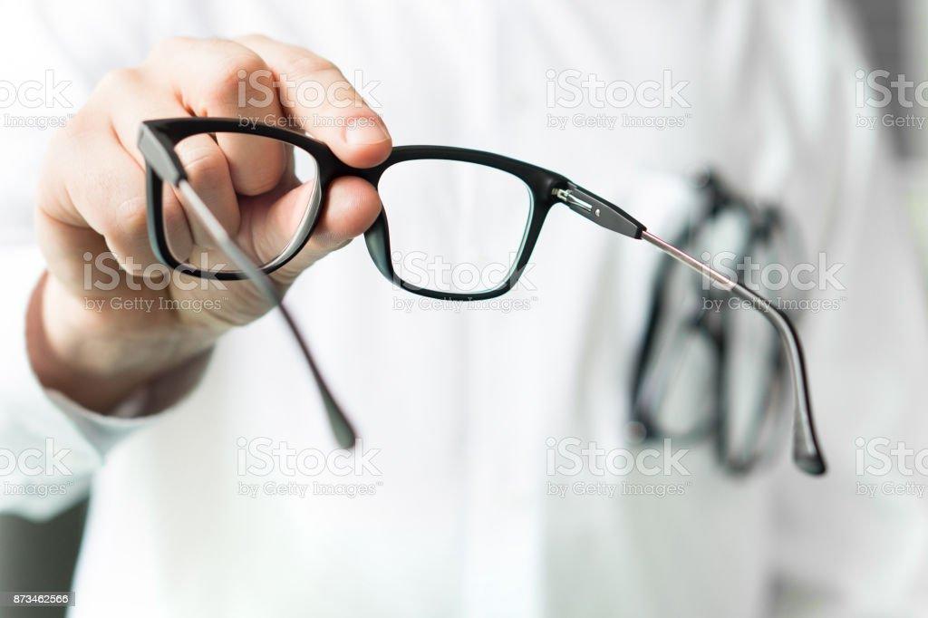 Optiker neue Gläser Kunden zu geben für testen und ausprobieren. Arzt zeigt Patienten Augenlinsen. – Foto
