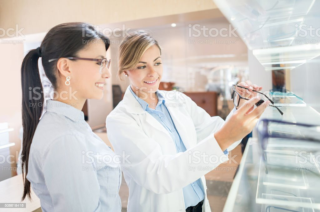 Optician helping patient shopping for glasses stock photo