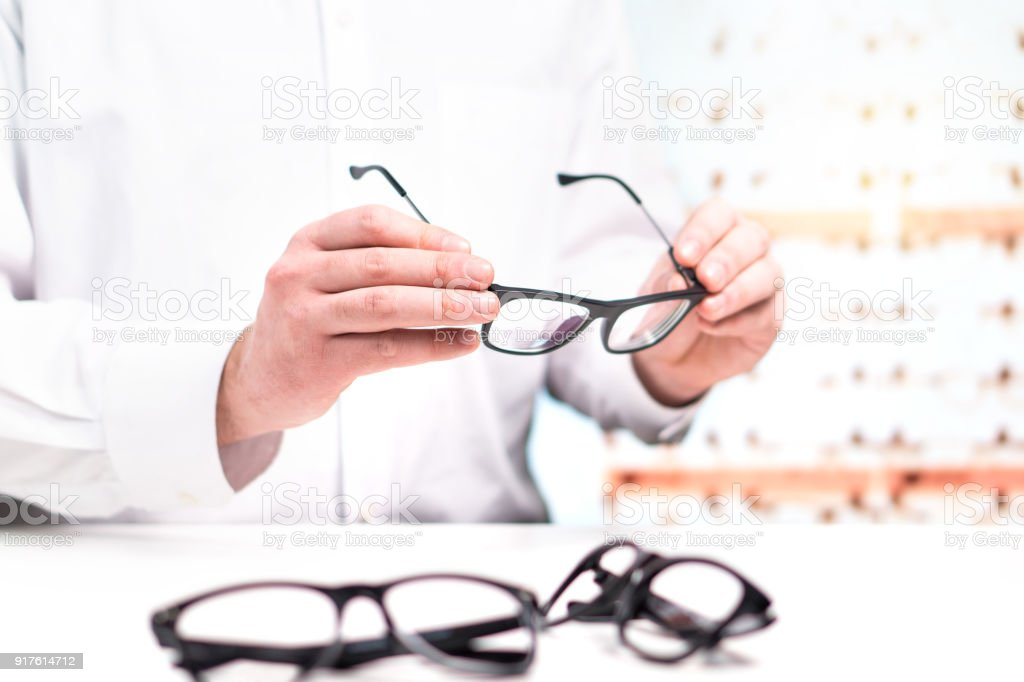 5ef8101acb2 Optician in store holding glasses. Eye doctor with lenses. Professional  optometrist in white coat with many eyeglasses. Shop interior. - Stock  image .