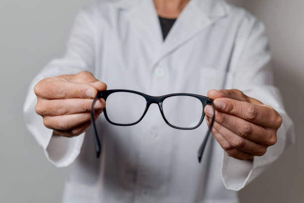 optician man bringing a pair of eyeglasses stock photo