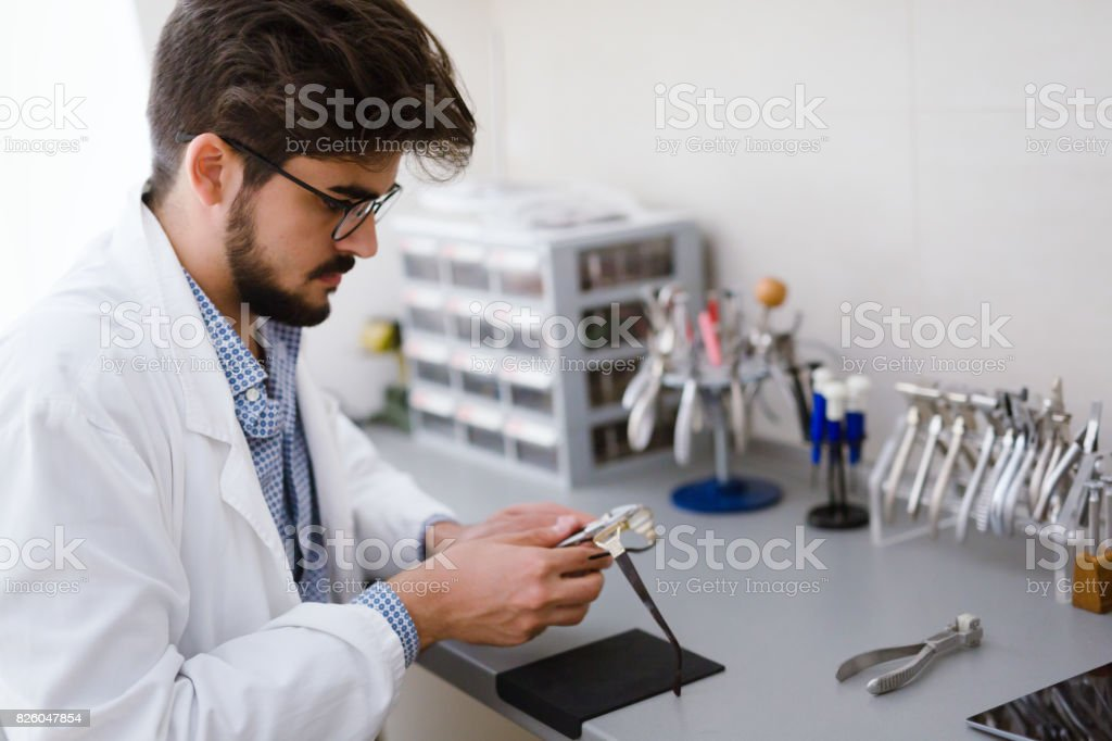 Optician repairing and fixing eye glasses stock photo