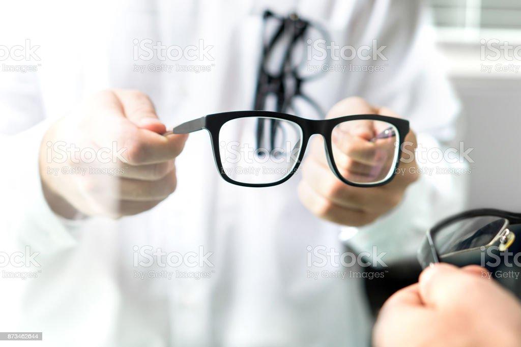 e35a8f41bf615c Opticien tonen nieuwe bril aan klant om uit te proberen. Oogarts patiënt  lenzen geven.