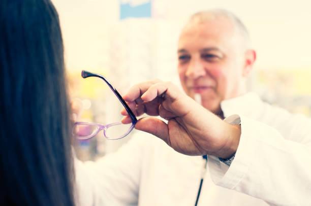 Optiker versucht Brille zu einem Kunden – Foto