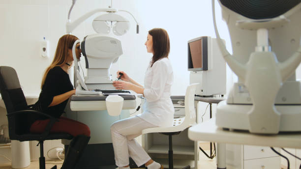 Optician with tonometer and patient at eye clinic, diagnostic stock photo