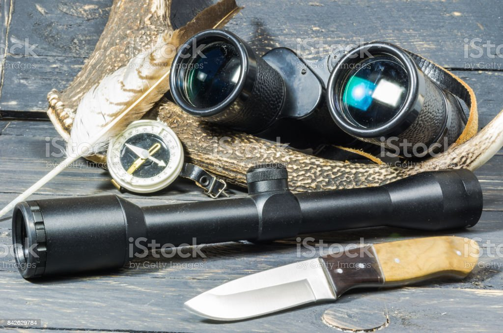 Optics for hunting. Hunter tools. Deer horn and bird feather. stock photo