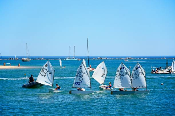 Optimist dinghies, Ferragudo, Portugal. People sailing in Optimist dinghy boats on the river Arade, Ferragudo, Algarve, Portugal, Europe. sailing dinghy stock pictures, royalty-free photos & images