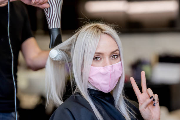 optimistic beautiful young woman with a face mask back in a hair salon at the end of the covid-19 pandemic - covid hair imagens e fotografias de stock