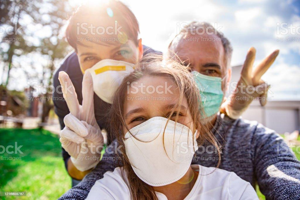 Optimistic Family selfie during Coronavirus emergency Optimistic Family selfie during Coronavirus emergency Adult Stock Photo