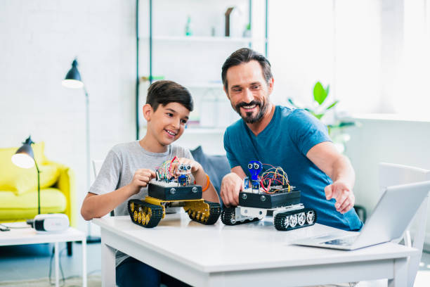Optimistic father and son enjoying their robotic hobby stock photo