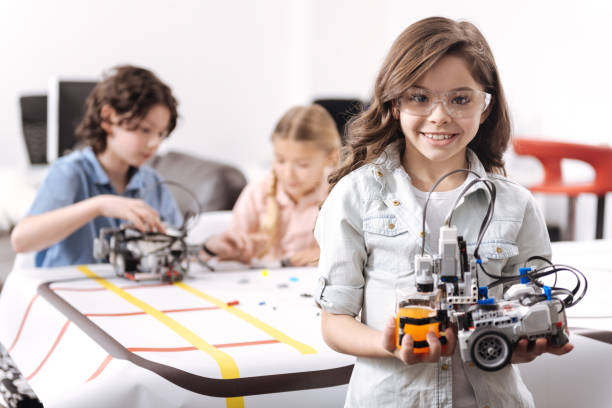 optimistische mädchen zeigt tech-projekt in der schule - lernfortschrittskontrolle stock-fotos und bilder