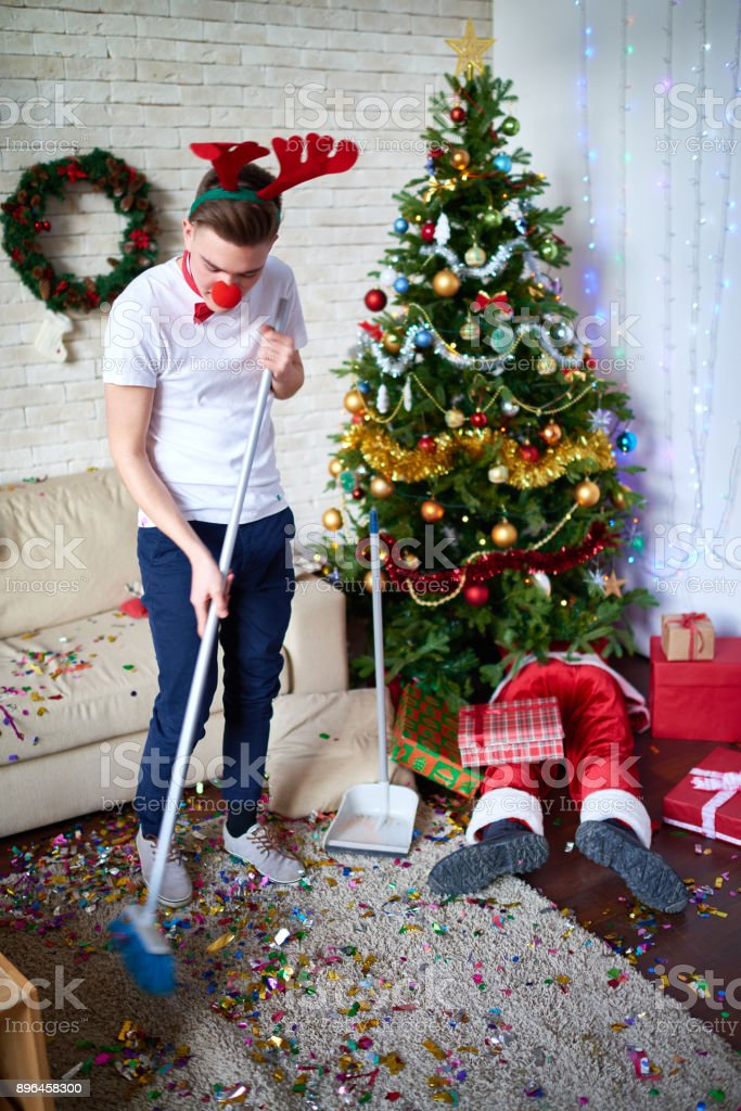 Optimistic guy cleaning room after Christmas party stock photo