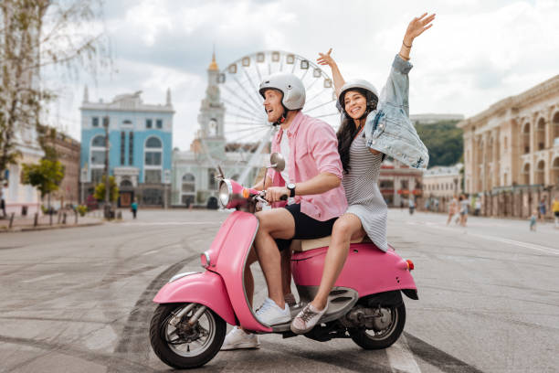 Optimistic jolly couple riding in city stock photo