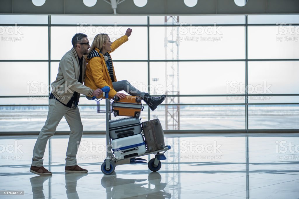 Optimistic male and female are walking to departure area stock photo