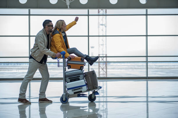 optimistic male and female are walking to departure area - luggage stock photos and pictures