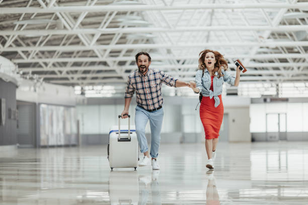 Optimistic male and girl running with baggage stock photo