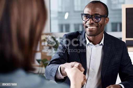 Nice to meet you. Portrait of cheerful young african manager in glasses is sitting at table and having firm handshake with new female employee. He is expressing gladness while looking at woman