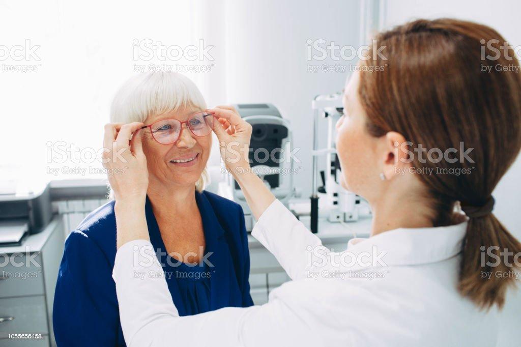 Optomerist setzt neue Brille auf Matue Frau Gesicht - Lizenzfrei Allgemeinarztpraxis Stock-Foto