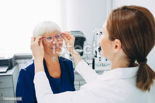 istock Optomerist is putting new glasses on matue woman face 1055656458