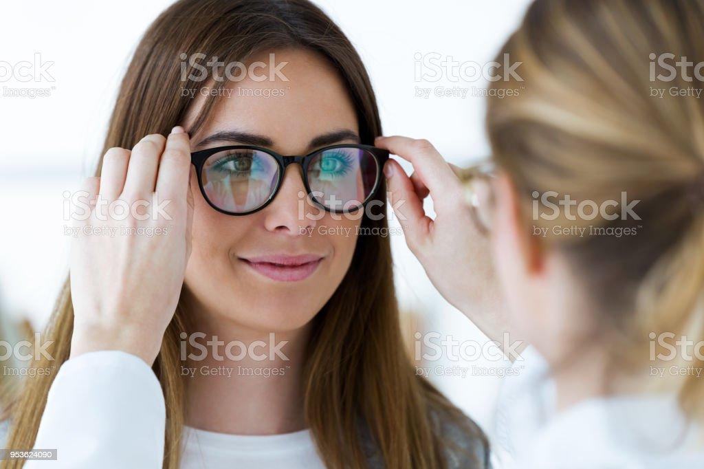Optometrist and pretty young woman choosing eyeglasses in optics. stock photo