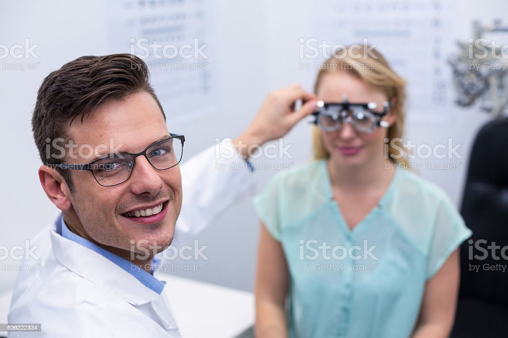 Optometrist examining female patient with phoropter stock photo