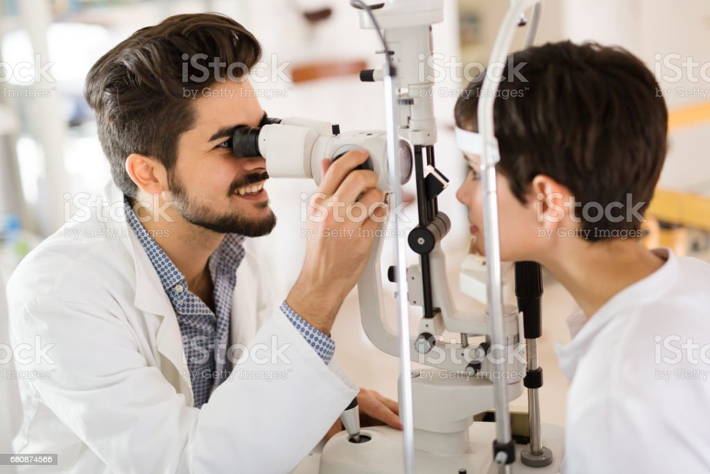 Optometrist examining patient in modern ophthalmology clinic royalty-free stock photo