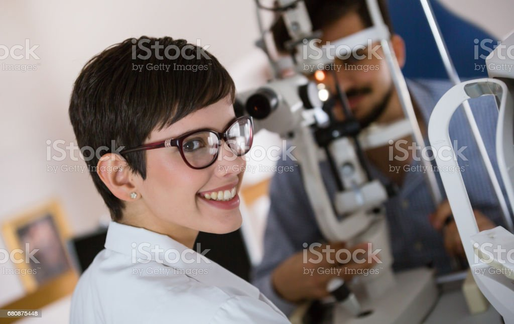 Optometrist examining patient in modern ophthalmology clinic stock photo