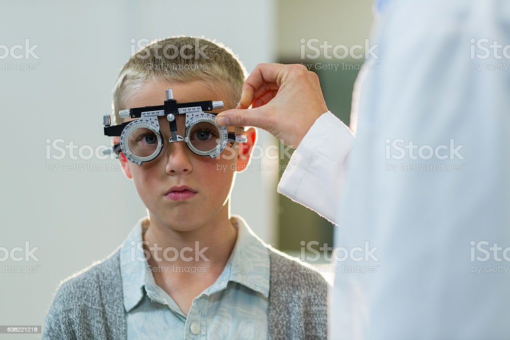 Optometrist examining young patient with phoropter stock photo