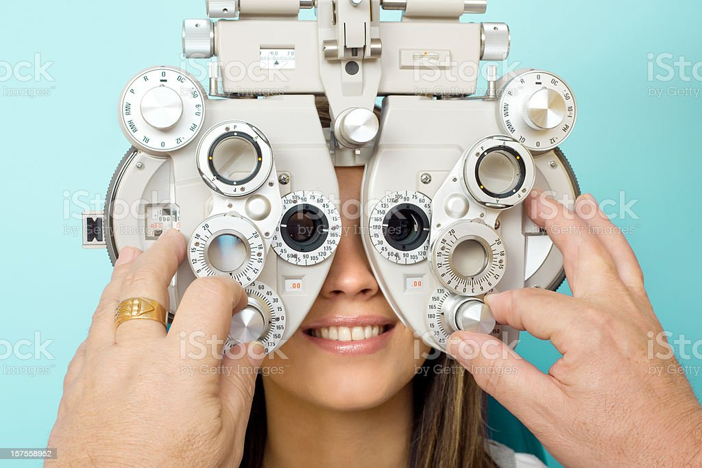 Optometrist Eye Exam Phoroptor Optometrist examines the eyes of a young woman patient with a phoroptor. Male hands adjusting dial on the phoroptor. Adjusting Stock Photo